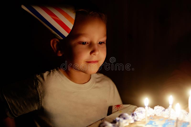 Boys birtday cake. Boy wearing birtday hat about to blow out candles royalty free stock photo