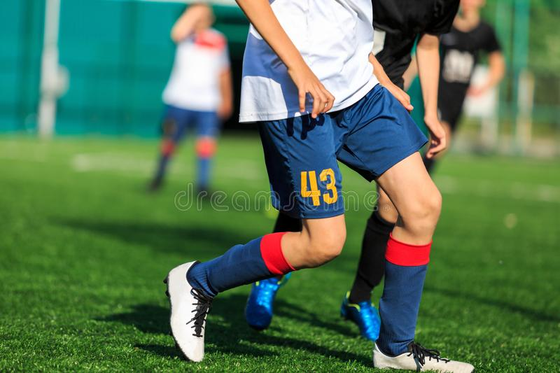 Boys at blue white sportswear run, dribble, attack on football field. Young soccer players with ball on green grass. Training royalty free stock photography