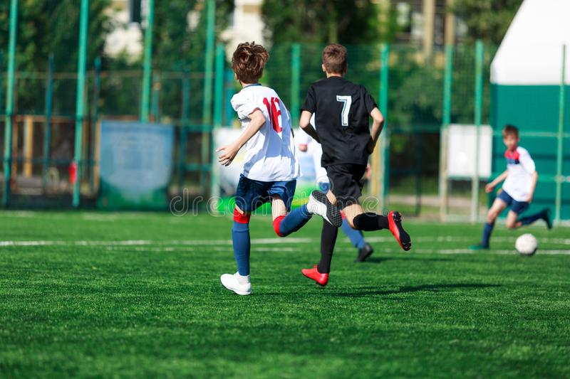 Boys at blue white sportswear run, dribble, attack on football field. Young soccer players with ball on green grass. Training stock image