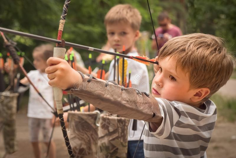 Boys with a bow and arrow. Children and sports. Boy with bow and arrow concentrated on target. Kid stared at target. Child directed arrow at a target. Bowman stock photo