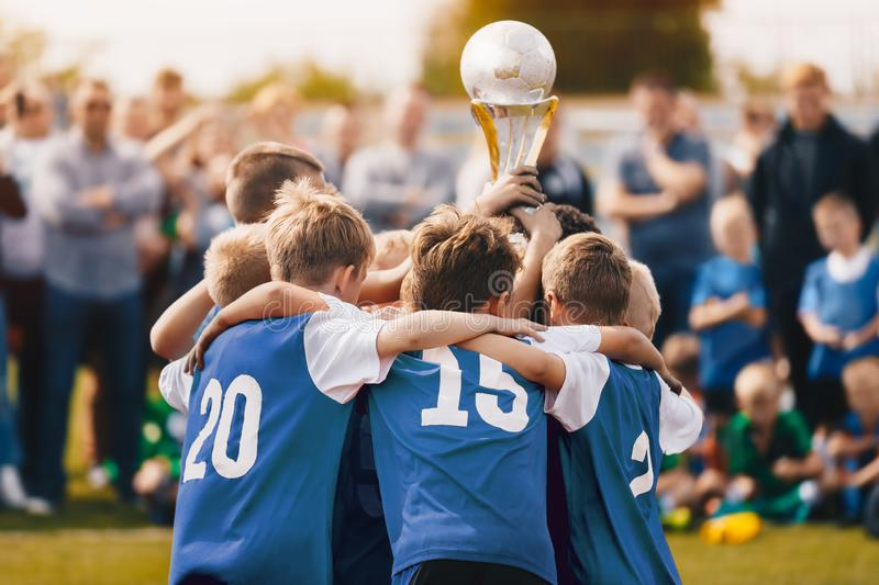 Boys Champion Sport Team. Kids Holding Winner Golden Cup. Children Rising Prize Cup. Boys in Blue Jersey Celebrating royalty free stock images