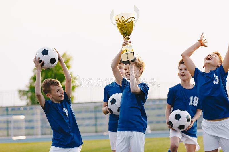 Boys are cheering for their team victory. Happy kids celebrating success in sports youth tournament. Boys holding golden cup. Football school tournament for royalty free stock photography