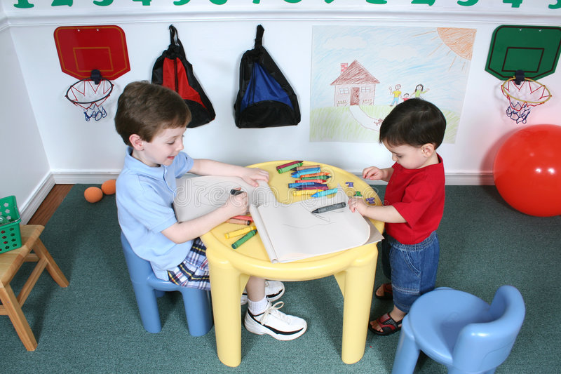 Boys Coloring at Preschool. Four year old and Two year old boys sharing crayons at preschool. Generic crayons used. Picture on wall not copyrighted. Shot with royalty free stock photography