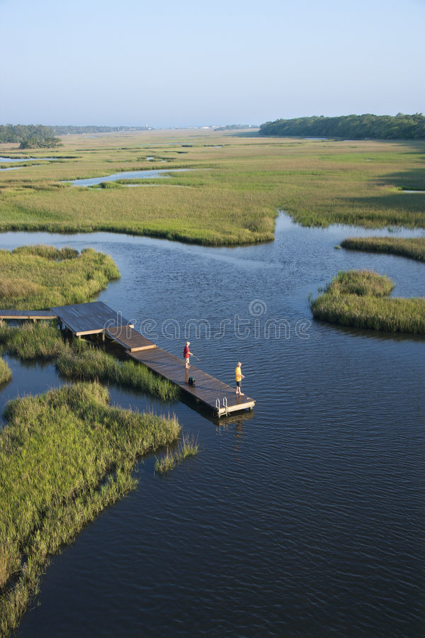 Boys on dock in marsh. royalty free stock photo