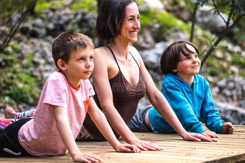 A woman trains with children in the yard royalty free stock image