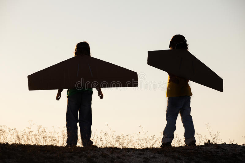 Boys dream of flying outdoors. Silhouette boy with cardboard boxes of wings against the sky dream of flying stock photography