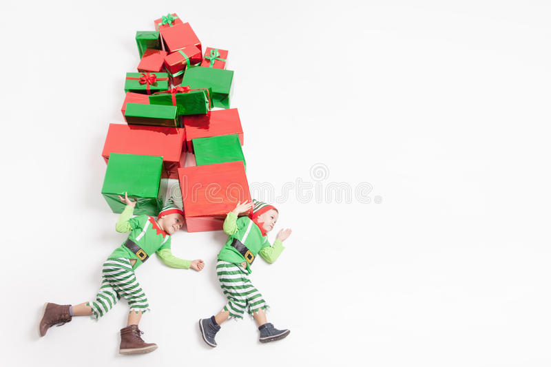 Boys dressed Elf costumes holding many gift boxes. Black Friday!. Funny two boys dressed in Elf costumes holding many gift boxes. Black Friday 2016! Celebrating stock photos
