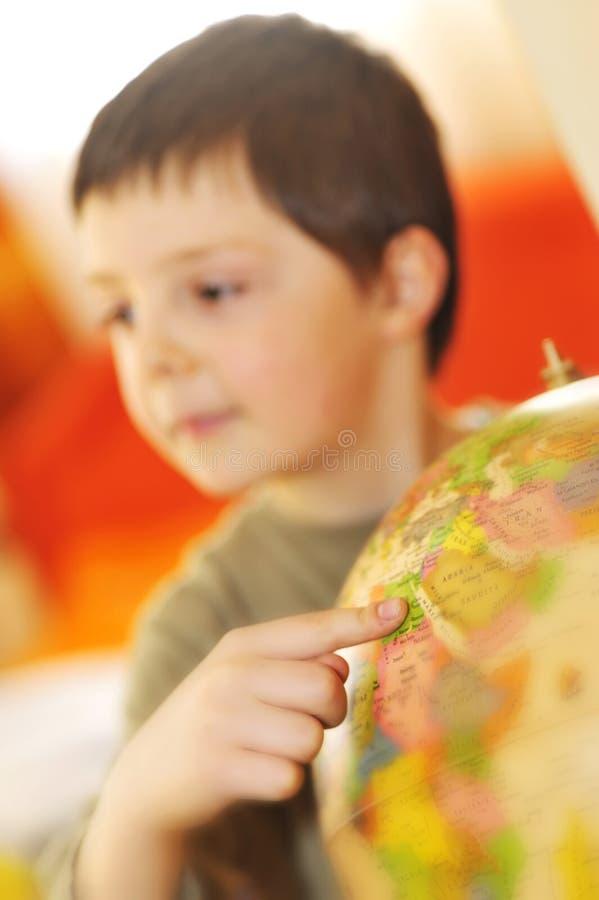 Boys finger pointing on world globe royalty free stock images