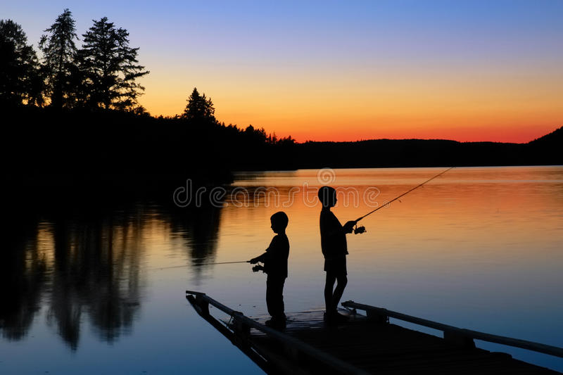 Boys Fishing. Two young boys fishing on a dock at sunset