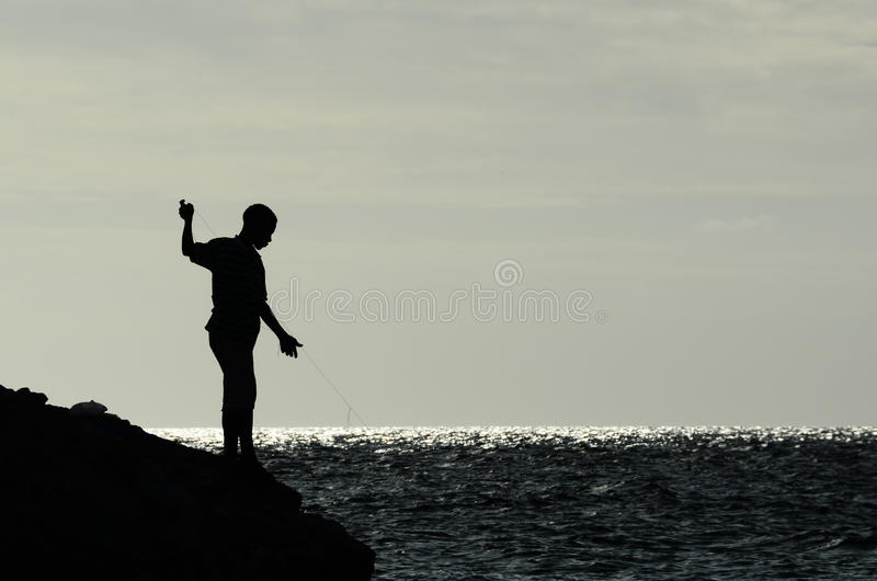 Boys fishing from rocky shore stock image