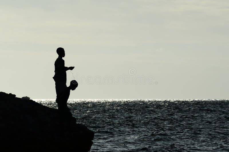 Boys fishing from rocky shore stock photo