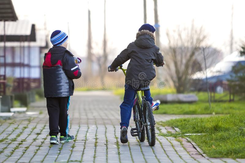 Boys friends on a bicycle outside. Children playing outdoors.  stock photos