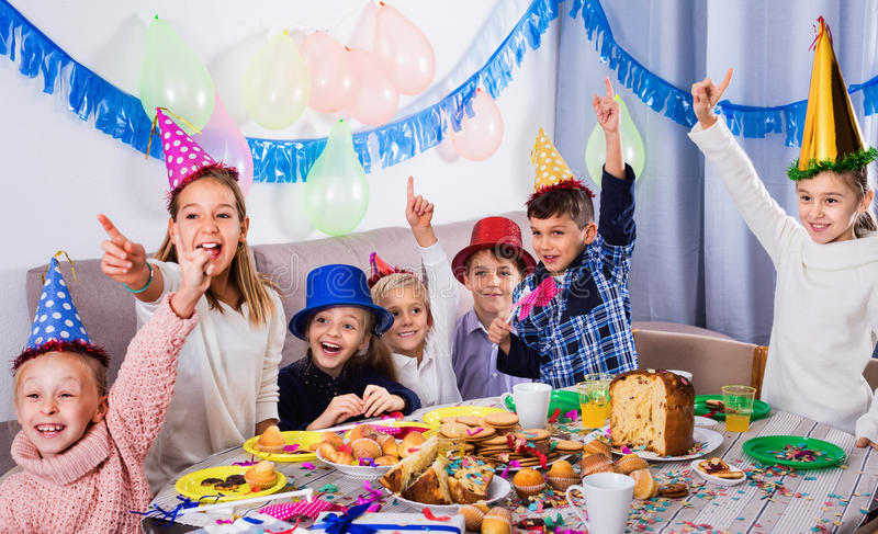 Boys and girls behaving jokingly during friend's birthday part. Glad smiling boys and girls behaving jokingly during friend's birthday party stock photography