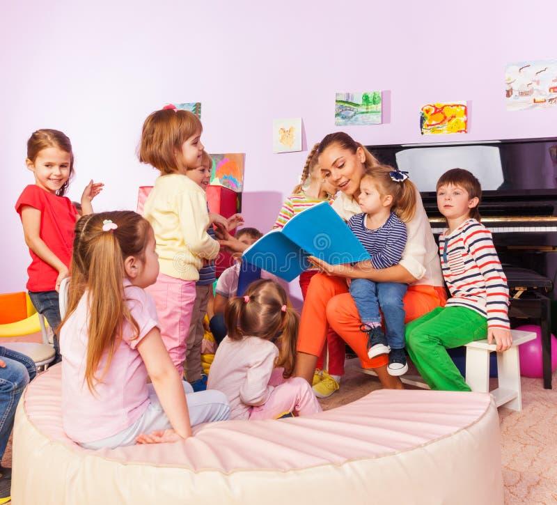 Boys and girls listen to teacher read book royalty free stock photos