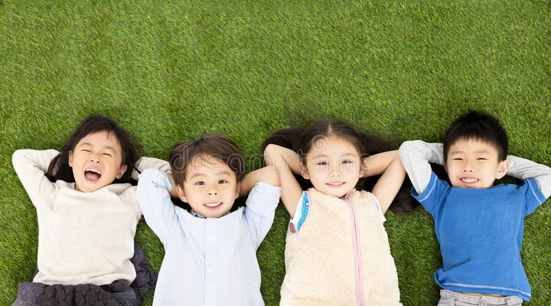 boys and girls lying on green grass stock photography