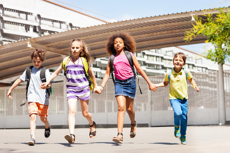 Excited kids run, hold hands near school building. Boys and girls run in front of the school yard happy holding hands smiling stock photos