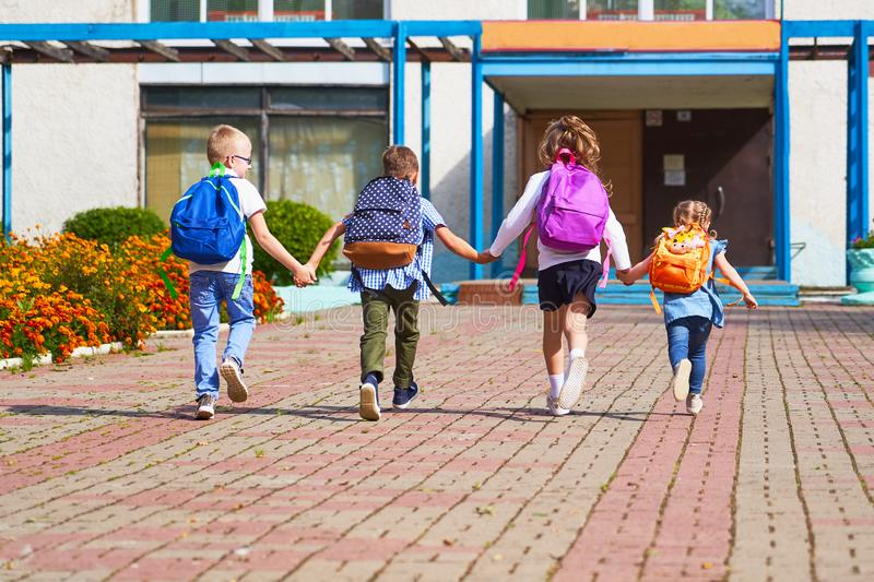 Boys and girls running to the elementary school stock photo