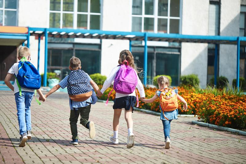 Boys and girls running to the elementary school royalty free stock photography