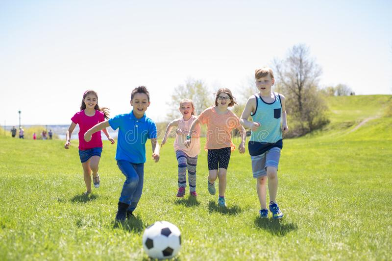 Boys and girls running towards football stock images