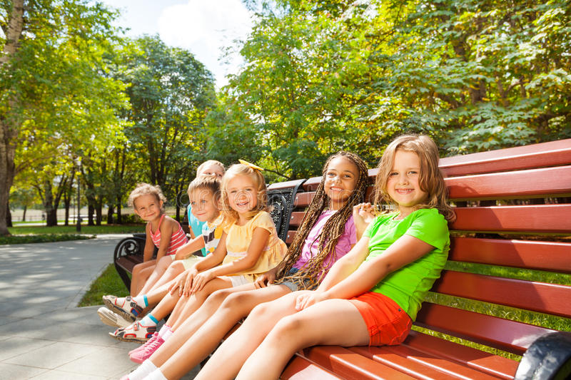 Boys and girls sitting on summer bench in park royalty free stock photos