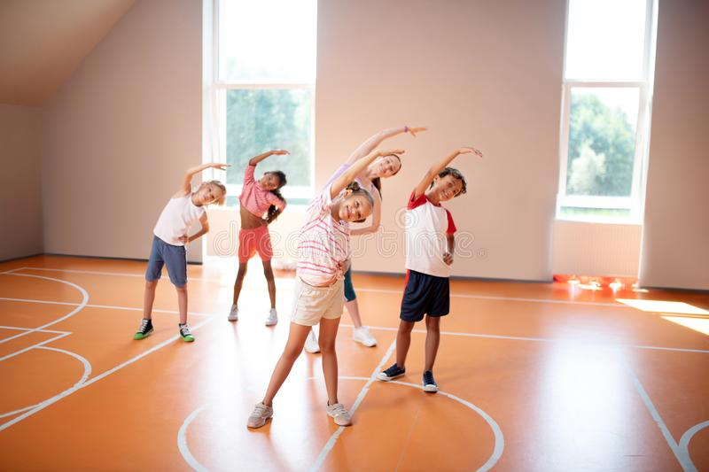 Boys and girls stretching with teacher at the PE lesson stock photography