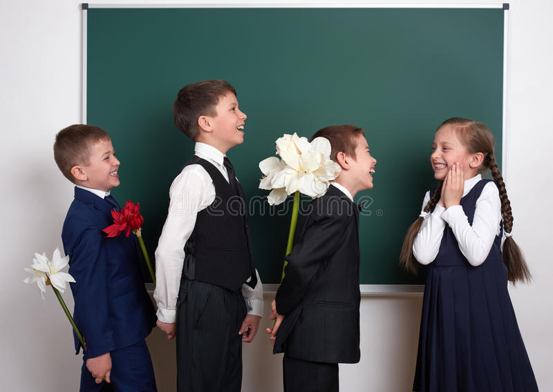 Boys giving girl flowers, elementary school child near blank chalkboard background, dressed in classic black suit, group pupil, ed royalty free stock images