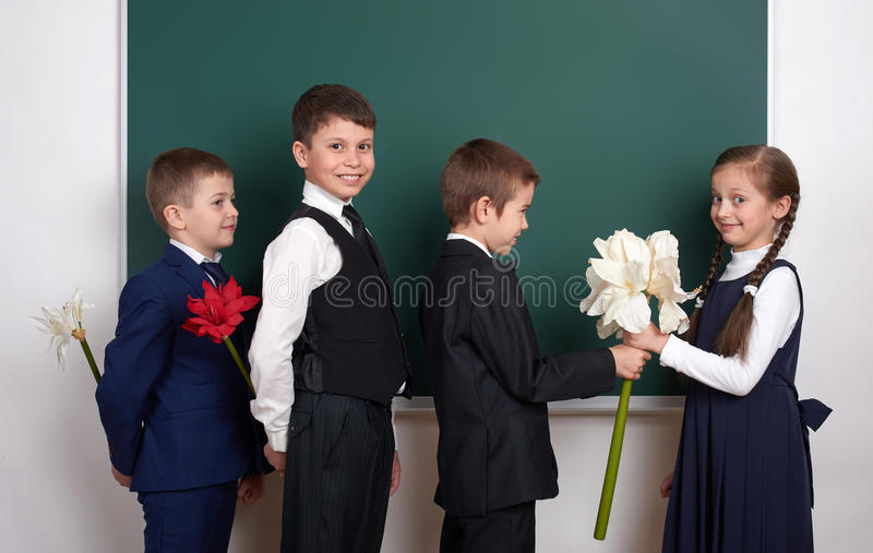 Boys giving girl flowers, elementary school child near blank chalkboard background, dressed in classic black suit, group pupil, ed royalty free stock image