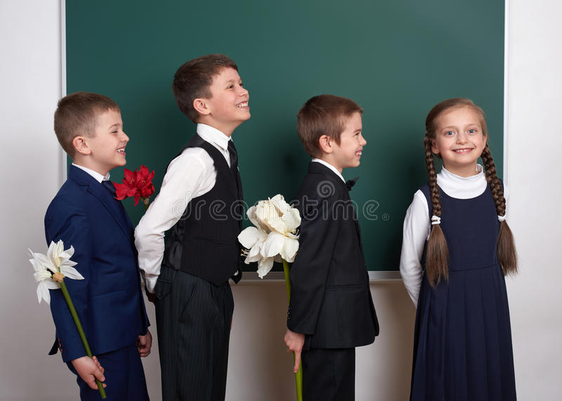 Boys giving girl flowers, elementary school child near blank chalkboard background, dressed in classic black suit, group pupil, ed royalty free stock photos