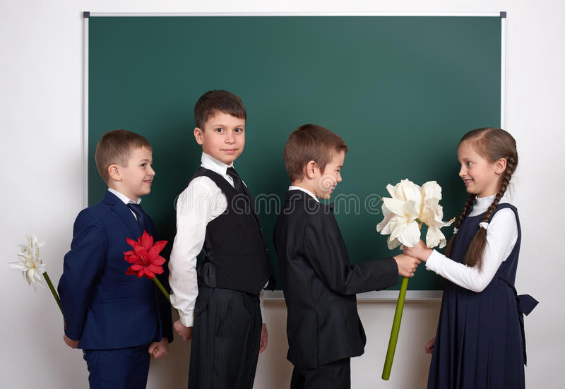 Boys giving girl flowers, elementary school child near blank chalkboard background, dressed in classic black suit, group pupil, ed. Ucation concept royalty free stock photo