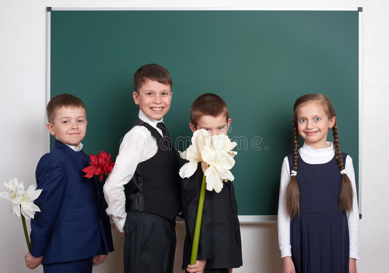 Boys giving girl flowers, elementary school child near blank chalkboard background, dressed in classic black suit, group pupil, ed stock photo