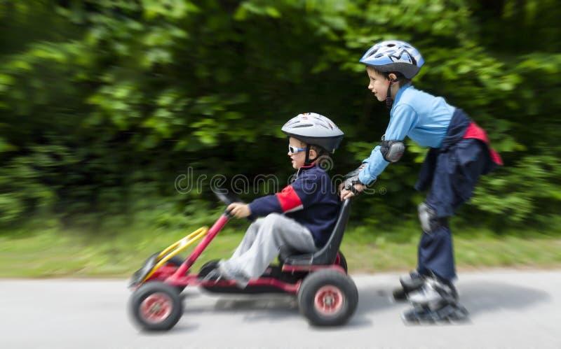 Boys gokart and roller blades royalty free stock photos