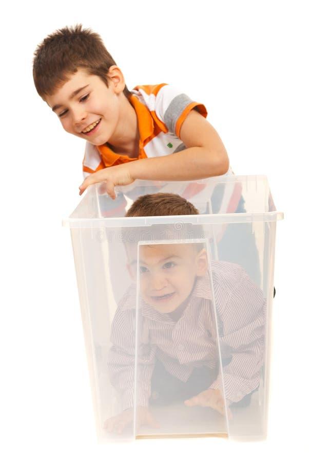 Boys having fun with a box stock photo