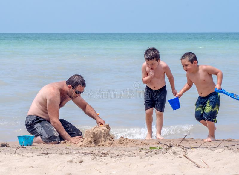 Boys help dad build a sand castle. Two young brothers help their dad build a sand castle on the shores of Lake Michigan in Michigan USA royalty free stock photo