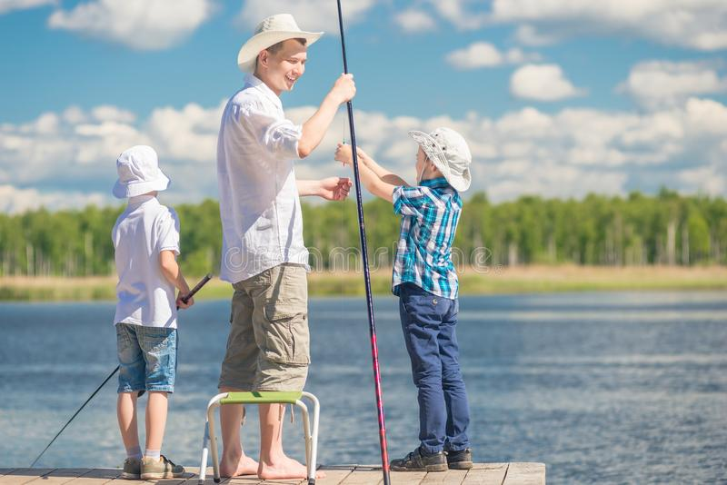 Boys with his father on the pier while fishing royalty free stock images