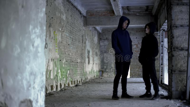 Boys in hoodie talking in ruined building, teenage gang, young criminals royalty free stock photography