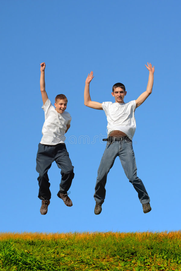 Boys jumping. Happy smiling youth two teenage boys jumping royalty free stock photo