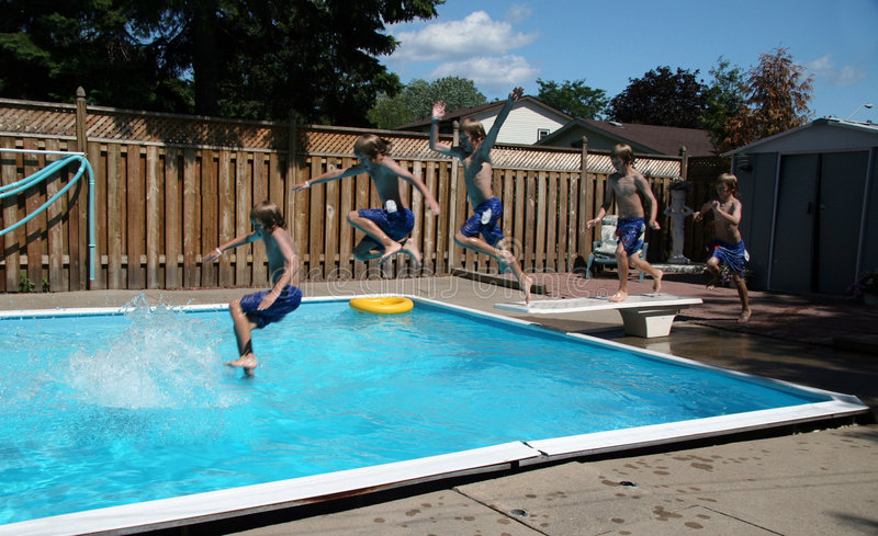 Boys Jumping into Pool. Five boys running onto diving board and jumping into swimming pool royalty free stock photo