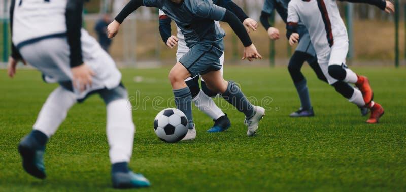 Boys Juniors in Action Play Football Soccer Match. Running Footballers Athletes. Boys Juniors in Action Play Football Soccer Match. Running Football Soccer stock photo