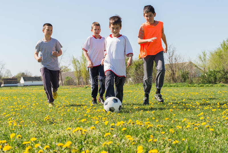 Boys kicking football royalty free stock images
