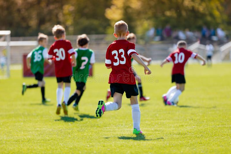 Boys kicking football on the sports field. An action sport picture of a group of kids playing soccer football tournament game royalty free stock photo
