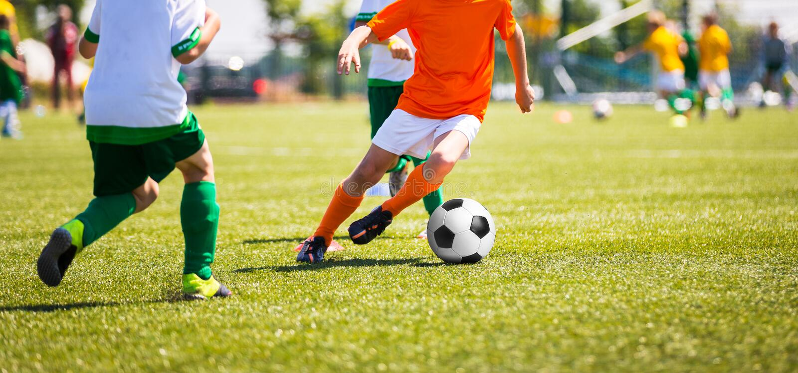Boys Kicking Soccer Ball. Children Soccer Team. Running soccer players. Boys Kicking Soccer Ball. Children Soccer Team. Kids Running with Ball on Football Pitch stock image