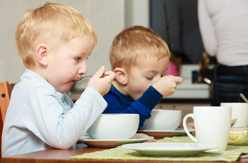Boys kids children eating corn flakes breakfast meal at the table. Two blond brothers boys kids children eating corn flakes breakfast morning meal at the table stock image
