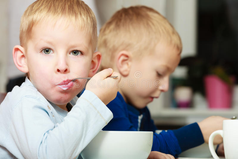 Boys kids children eating corn flakes breakfast meal at the table. Two blond brothers boys kids children eating corn flakes breakfast morning meal at the table stock images