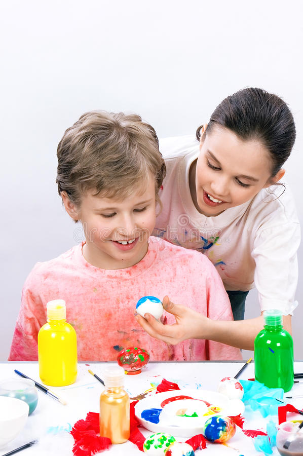Boys painting eggs for Easter stock images