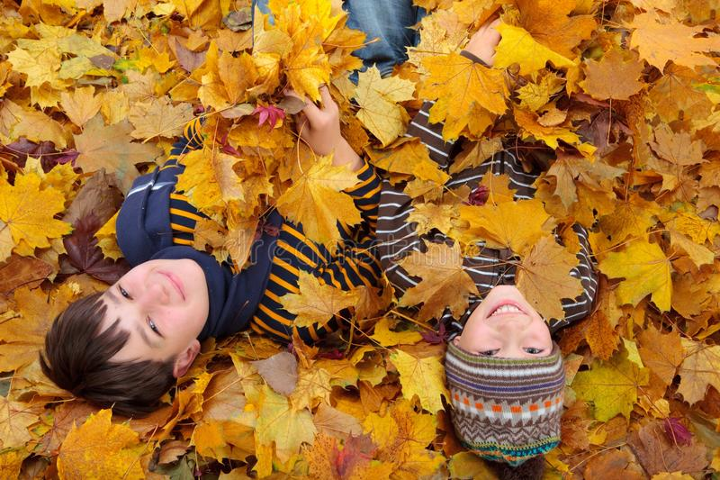 Boys in pile of leaves stock photos