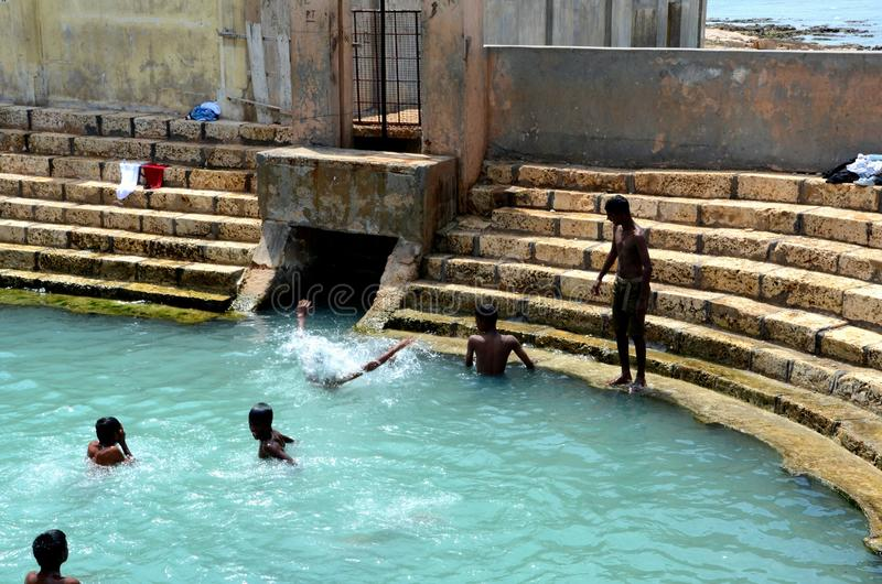 Boys play and bathe in Keerimalai fresh water spring tank by ocean water Jaffna Sri Lanka. Jaffna, Sri Lanka - February 19, 2017: A bathing tank full of boys in stock photos