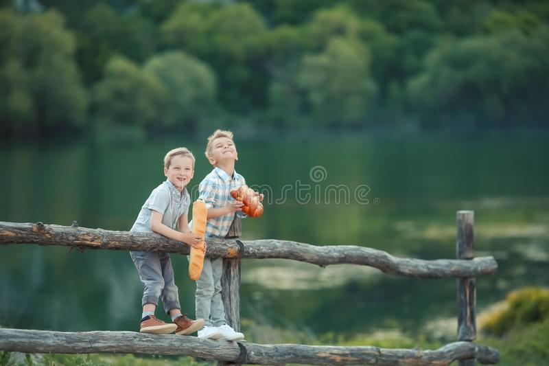 Boys playing in the banks of the pond.  stock photo