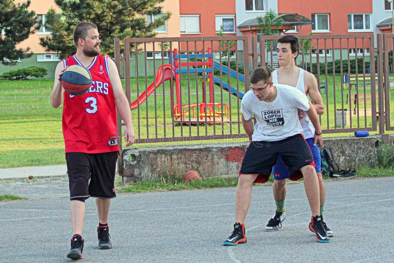 Boys are playing basketball on court in local settlement in Slovakia royalty free stock photography