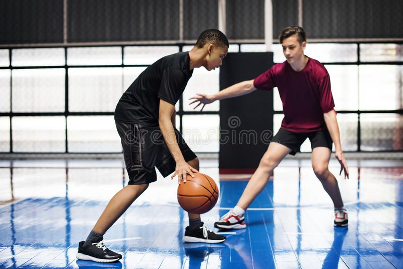 Boys playing basketball together on the court. Two teenage boys playing basketball together on the court stock image