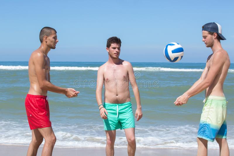 3 boys playing beach volleyball. Beach stock photo